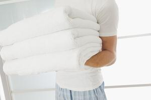 Close up of a guy holding clean towels.