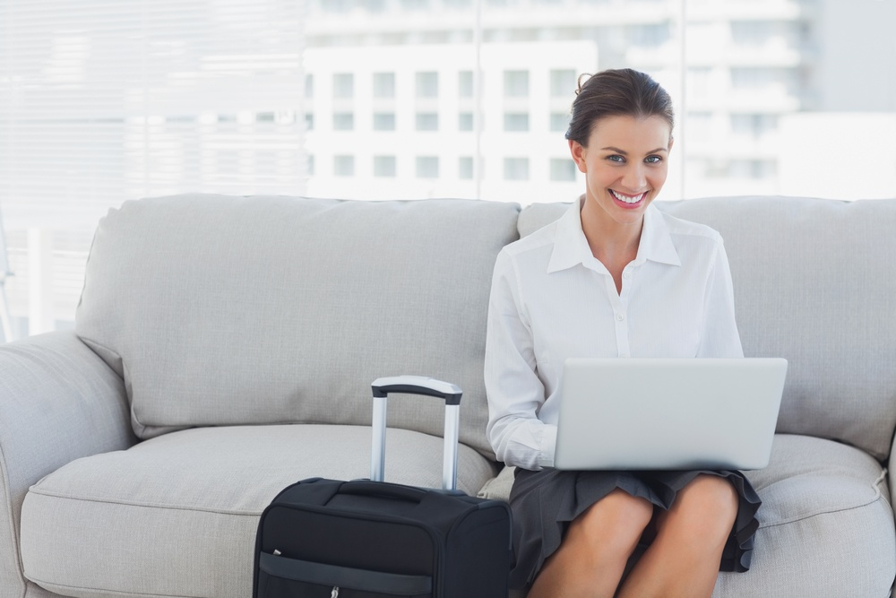 Happy businesswoman sitting on the couch using laptop with her suitcase beside her