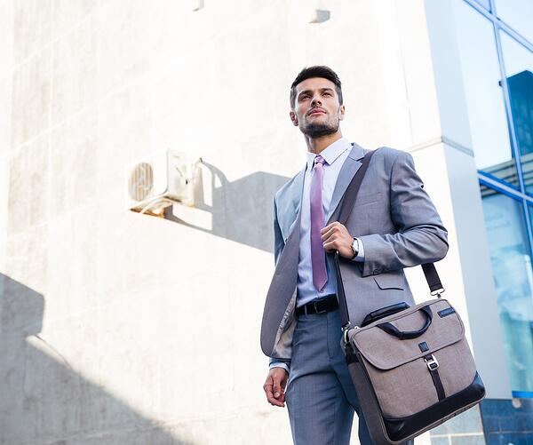 Portrait of a handsome businessman standing outdoors near office building