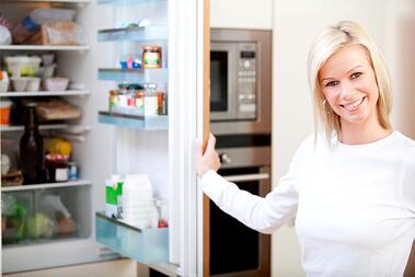 Woman at home looking inside the fridge and smiling